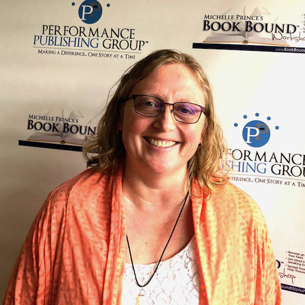 woman in front of book bound banner in orange shawl and white shirt