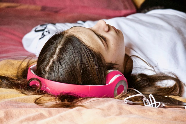 girl laying with red headphones and white shirt